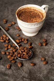 Nahaufnahmetasse kaffee mit gebratenen bohnen