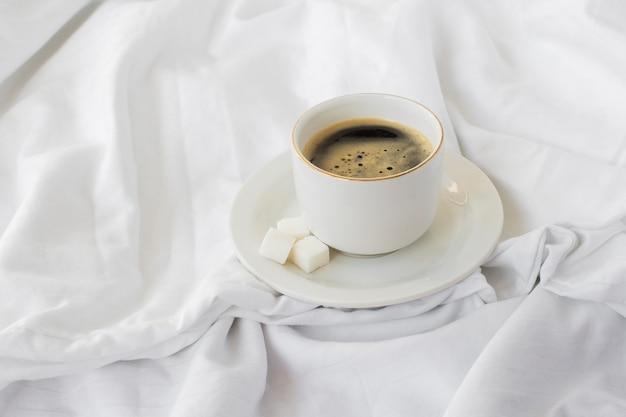 Nahaufnahmetasse kaffee mit zuckerwürfeln
