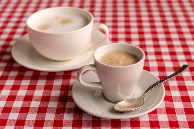 Nahaufnahmetassen kaffee mit kariertem hintergrund