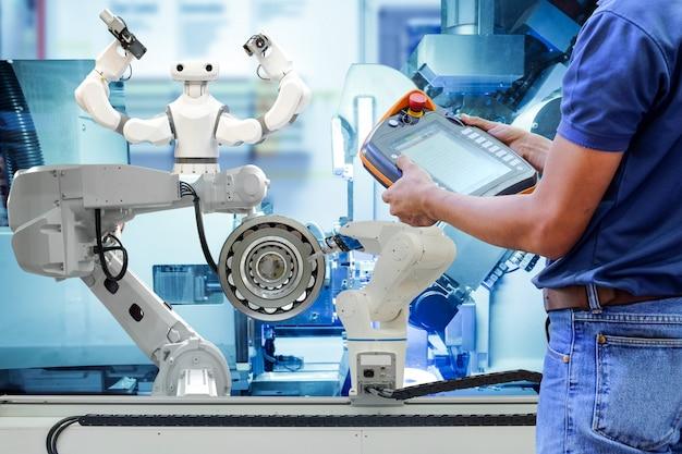 Nahaufnahmetechniker mann, der drahtlose fernbedienung verwendet, um programm zur steuerung der industrierobotik einzustellen, um automatisierung über linienproduktion auf smart factory zu arbeiten