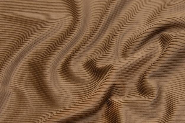 Nahaufnahmetextur aus natürlichem braunem stoff oder stoff in derselben farbe. gewebestruktur aus natürlicher baumwolle, seide oder wolle oder leinentextilmaterial. samt-leinwand-hintergrund.