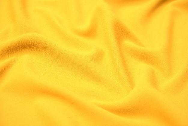 Nahaufnahmetextur aus natürlichem orangefarbenem oder gelbem stoff oder stoff in derselben farbe. gewebestruktur aus natürlicher baumwolle, seide oder wolle oder leinentextilmaterial. gelber leinwandhintergrund.