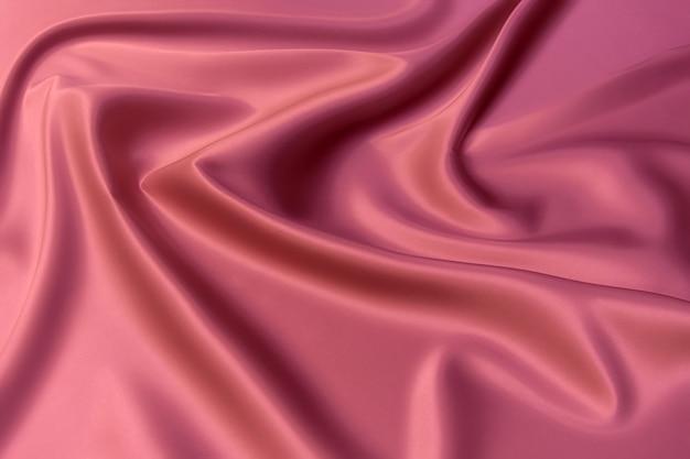 Nahaufnahmetextur aus natürlichem rotem oder rosa stoff oder stoff in derselben farbe. gewebestruktur aus natürlicher baumwolle, seide oder wolle oder leinentextilmaterial. rote leinwand hintergrund.