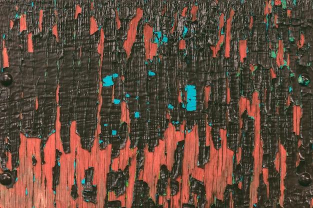 Nahaufnahmetextur von abblätternder farbiger farbe, braune holzwand.