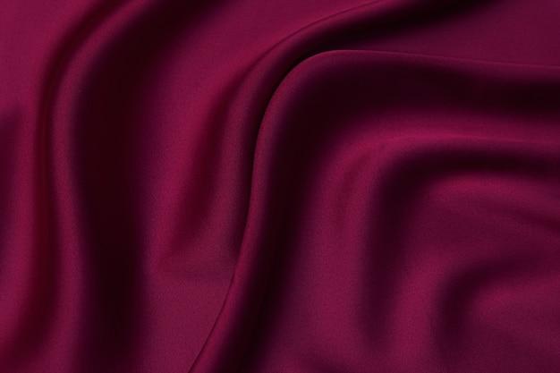 Nahaufnahmetextur von natürlichem rotem oder burgunderrotem stoff oder stoff in derselben farbe. gewebestruktur aus natürlicher baumwolle, seide oder wolle oder leinentextilmaterial. roter und orangefarbener leinwandhintergrund.