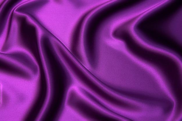 Nahaufnahmetextur von natürlichem violettem stoff oder stoff in der gleichen farbe. gewebestruktur aus natürlicher baumwolle, seide oder wolle oder leinentextilmaterial. roter und orangefarbener leinwandhintergrund.