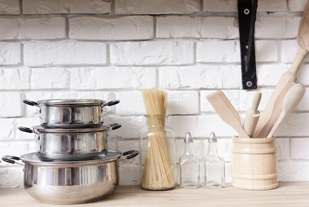 Nahaufnahmetöpfe und küchengeräte auf tischplatte