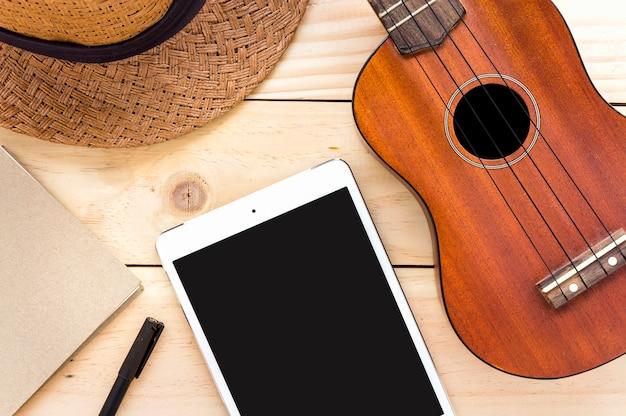 Nahaufnahmeukulele, -tablet-computer und -notizbuch auf hölzernem hintergrund. über licht