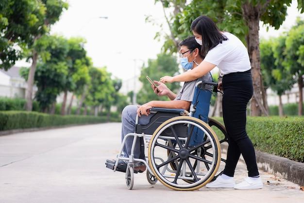 Nahaufnahmeunterstützung oder betreuer, die behinderten älteren patienten helfen, die auf einem rollstuhl sitzen junge frau, die hilft, einen behinderten alten mann in einem wagen älteres gesundheitskonzept zu pflegen