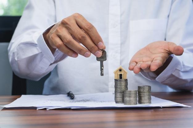 Nahaufnahmeverkäufer, der nach hause schlüssel zum geschäftsverkaufsimmobilienmietkonzept hält