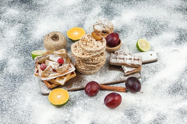 Nahaufnahmewaffeln und reiswaffeln mit zitrusfrüchten, zimt und keksen auf dunkelgrauer marmoroberfläche. horizontal