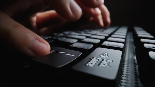 Nahaufnahmeweichheitsfinger, der auf tastatur schreibt.