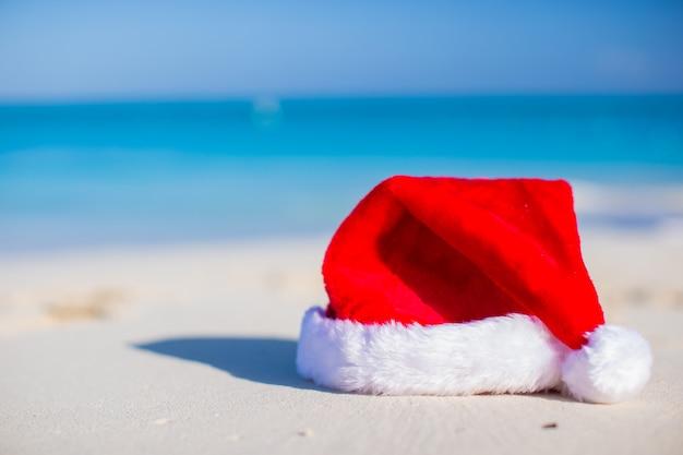 Nahaufnahmeweihnachtshut auf einem weißen sandigen strand