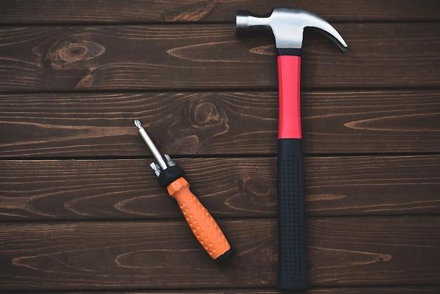 Nahaufnahmewerkzeuge als hammer und schraubendreher auf einem hölzernen hintergrund. arbeitskonzept. freier copyspace