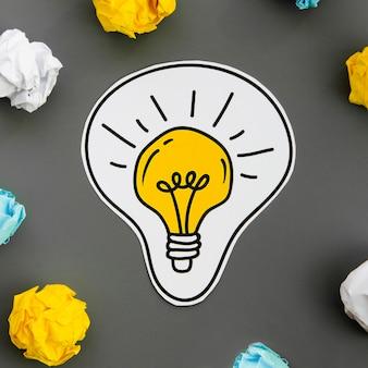 Nahaufnahmezeichnung einer glühlampe und des zerknitterten papiers