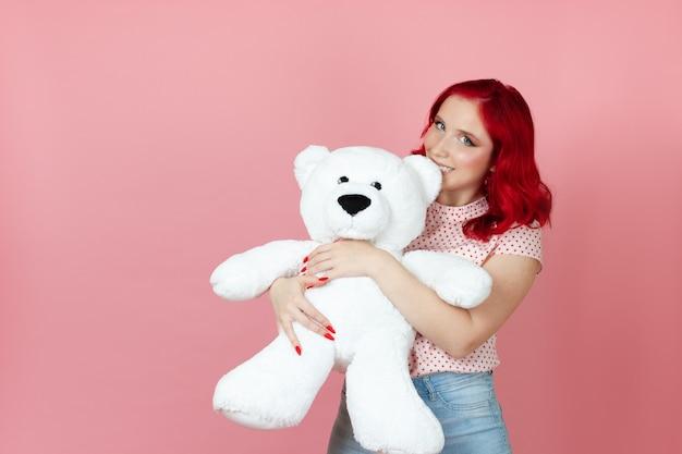 Nahe, freche, verspielte frau mit roten haaren beißt das ohr eines großen weißen teddybären