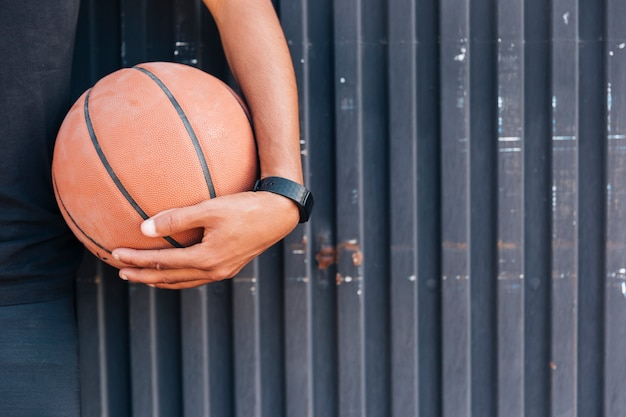 Nahe hohe hand der ernte, die basketball hält