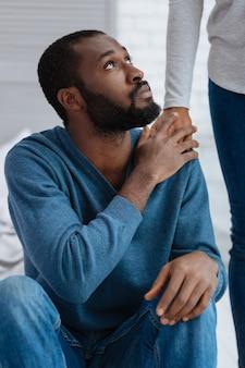 Nahe person. trauriger emotionaler junger mann, der sich aufgrund der unterstützung seiner geliebten frau besser fühlt