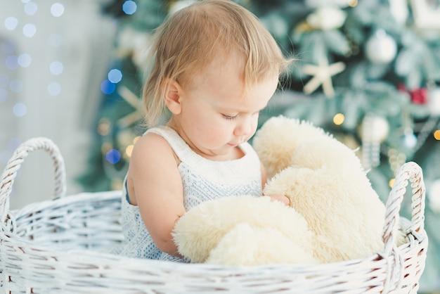 Nahe verzierter weihnachtsbaum des schönen mädchens mit hölzernem schaukelpferd des spielzeugs. frohes neues jahr. portrait kleines mädchen.