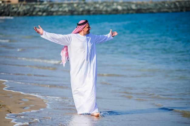 Naher osten gekleideter arabischer mann wirft vor seeküste auf.