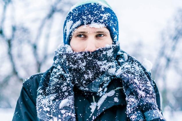 Nahes aufgerichtetes man'sace mit dem schal bedeckt durch schnee an einem wintertag