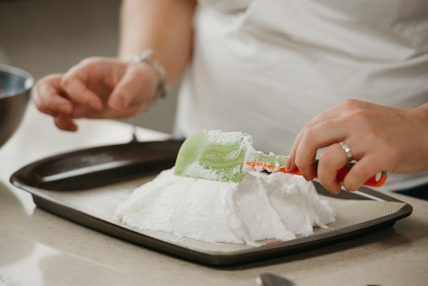 Ð nahes foto der hände einer jungen frau, die mit einem schulterblatt die form eines riesigen baisers auf einem tablett verbessert. ein mädchen bereitet sich darauf vor, eine köstliche zitronenbaisertorte zu kochen.