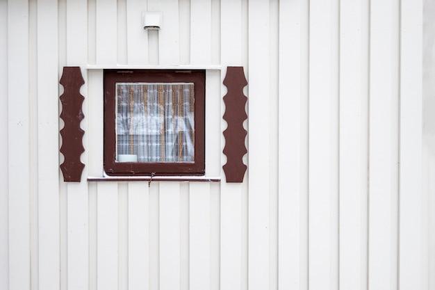 Nahes hölzernes fenster des außenraums mit vorhang auf bauholzwandhaus
