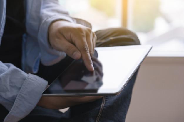 Nahes hohes der mann des digitalen tablet-computers, der tablette verwendet, übergibt den mann, der mehrere dinge gleichzeitig tut