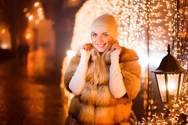 Nahes hohes porträt im freien der jungen glücklichen lächelnden frau, die auf straße aufwirft. schneefall, festliche girlande.