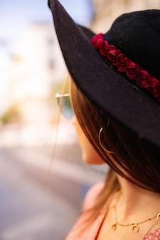 Nahes hohes porträt im freien der schönen jungen frau, die blaue katzenauge-sonnenbrille und -hut aufwirft in der stadtstraße trägt. weibliche frühlingsmode.