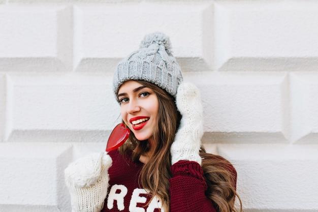 Nahes hübsches mädchen mit langen haaren im marsala-pullover auf grauer wand. sie trägt weiße handschuhe, eine graue strickmütze, hält einen roten herzlutscher und lächelt.