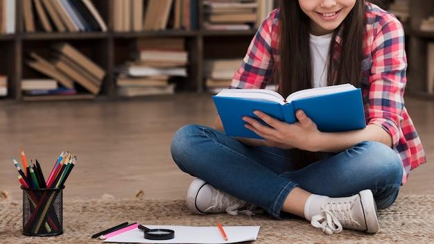 Nahes junges mädchen, das einen roman liest