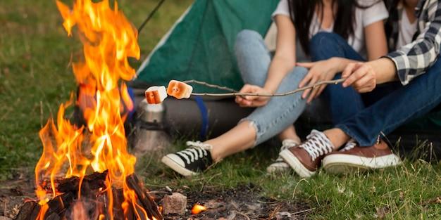 Nahes junges paar, das lagerfeuer genießt