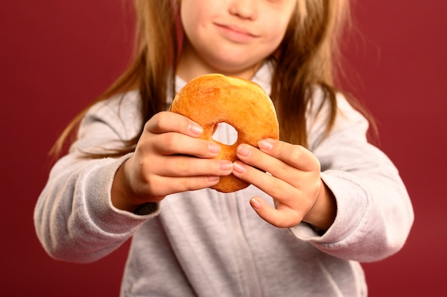 Nahes nettes junges mädchen, das donut hält