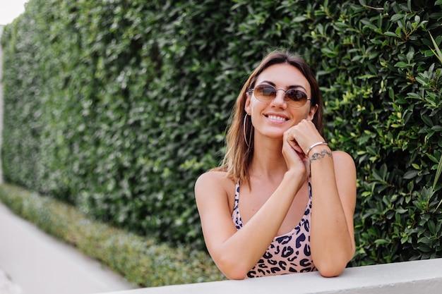 Nahes porträt der europäischen frau im leopardenoberteil und in der sonnenbrille und in den runden ohrringen auf grüner buschwand