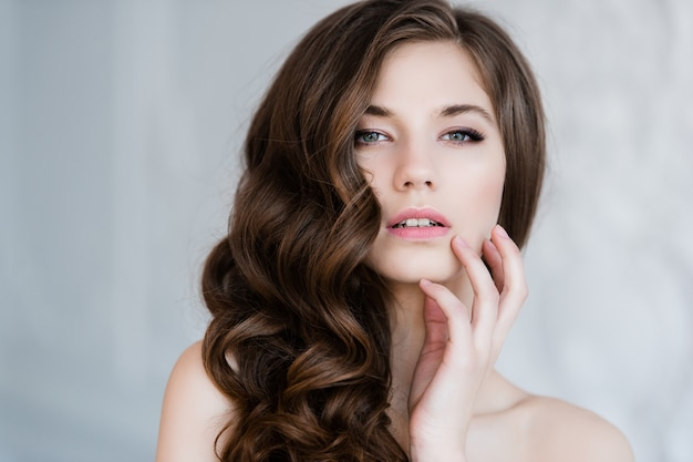 Nahes porträt der schönen lächelnden brautfrau mit dem langen lockigen haar, das im hochzeitskleid am innenraum und am lächeln aufwirft. innenporträt der schönheit.