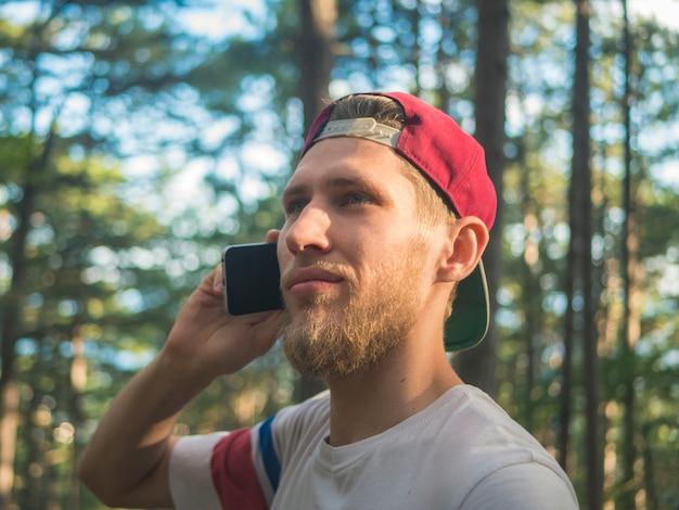 Nahes porträt des jungen bärtigen hippies in der kappe sprechend über das telefon, das in naturfrest in europa die schweiz geht