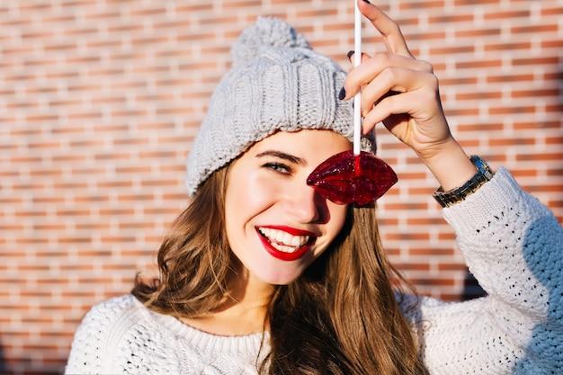 Nahes porträtporträt hübsches brünettes mädchen mit langen haaren in der strickmütze, die spaß mit den karamellroten lippen an der wand draußen hat. sie lächelt .