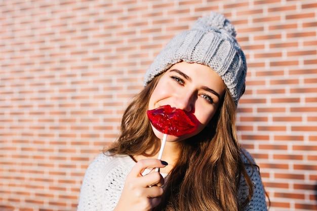 Nahes porträtporträt hübsches junges mädchen mit langen haaren mit roten lippen des lutschers an der wand außerhalb. sie trägt eine strickmütze und lächelt.