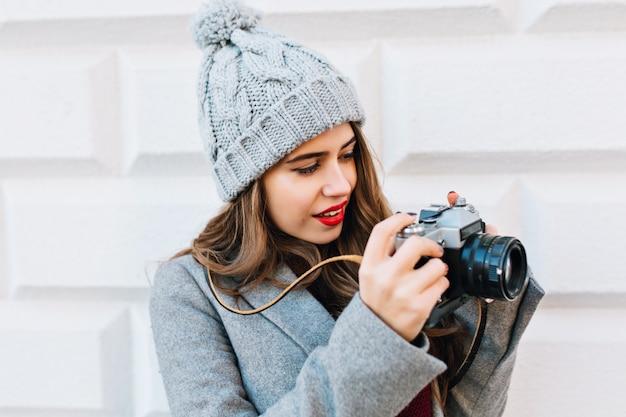 Nahes porträtporträt junges mädchen mit langen haaren im grauen mantel auf grauer wand im freien. sie wird vor der kamera in händen betrachtet.