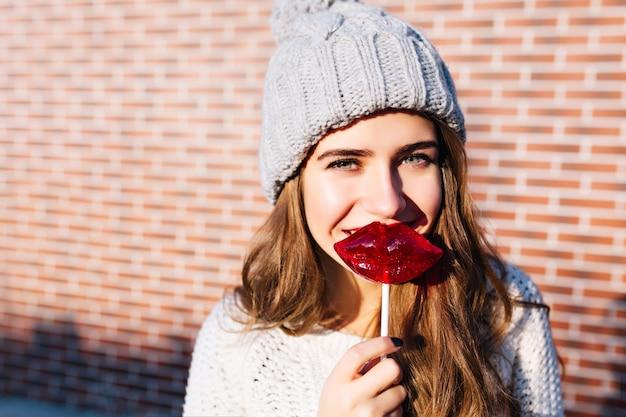Nahes porträtporträt junges mädchen mit langen haaren im strickhut mit roten lippen des lutschers an der wand außerhalb. sie lächelt .