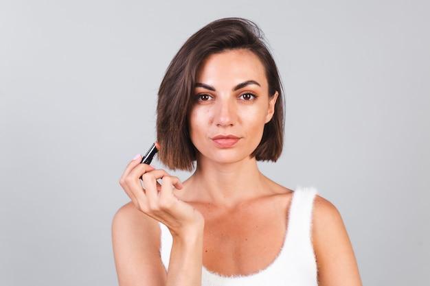 Nahes schönheitsporträt der frau mit make-up und braunem lippenstift auf grauer wand