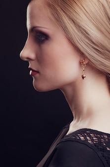 Nahes weibliches modell mit blondem haar mit make-up und eleganter frisur auf schwarzem hintergrund.
