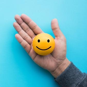 Nahkampfhand, die gelben emoticonball auf blauem farbhintergrund hält
