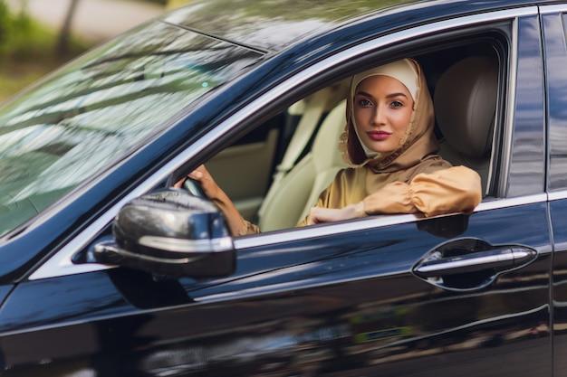 Nahöstliche frau, die ein auto fährt, das vorwärts schaut Premium Fotos