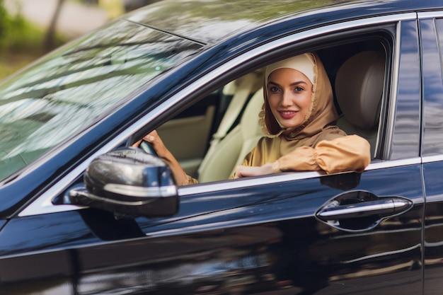 Nahöstliche frau, die ein auto fährt, das vorwärts schaut