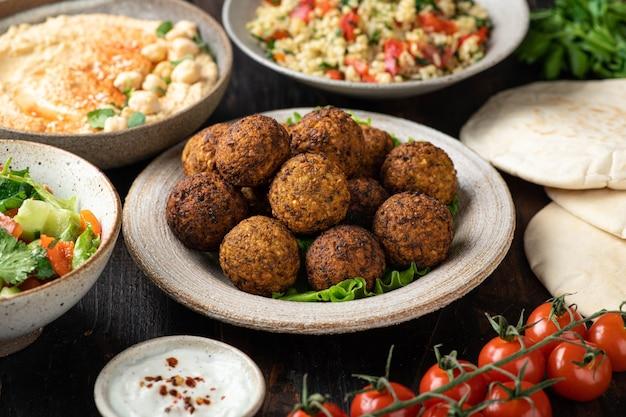 Nahöstliche oder arabische küche falafel hummus tabouleh pita und gemüse auf holzhintergrund selektiver fokus