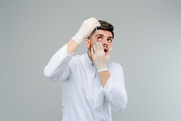 Nahöstlicher arztaugenarzt in den handschuhen, die seine augen mit tropfen behandeln