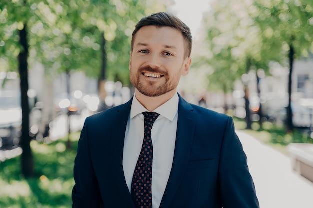 Nahporträt eines lächelnden, gutaussehenden jungen bärtigen mannes in dunkelblauem anzug, der an einem sonnigen tag entlang der grünen gasse im stadtzentrum draußen spaziert, glücklich, heute bei der arbeit befördert zu werden