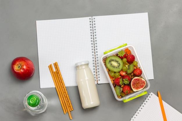 Nahrhafte brotdose mit früchten auf offenem notizbuch mit milchflasche, apfel, flasche wasser und stiften
